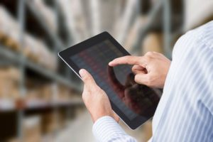 man checking inventory on computer tablet against warehouse background