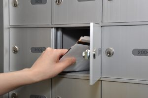 woman's hand reaching into mailbox for letters
